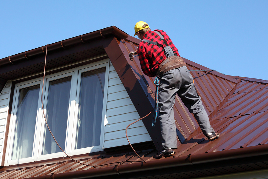 man spray painting the roof